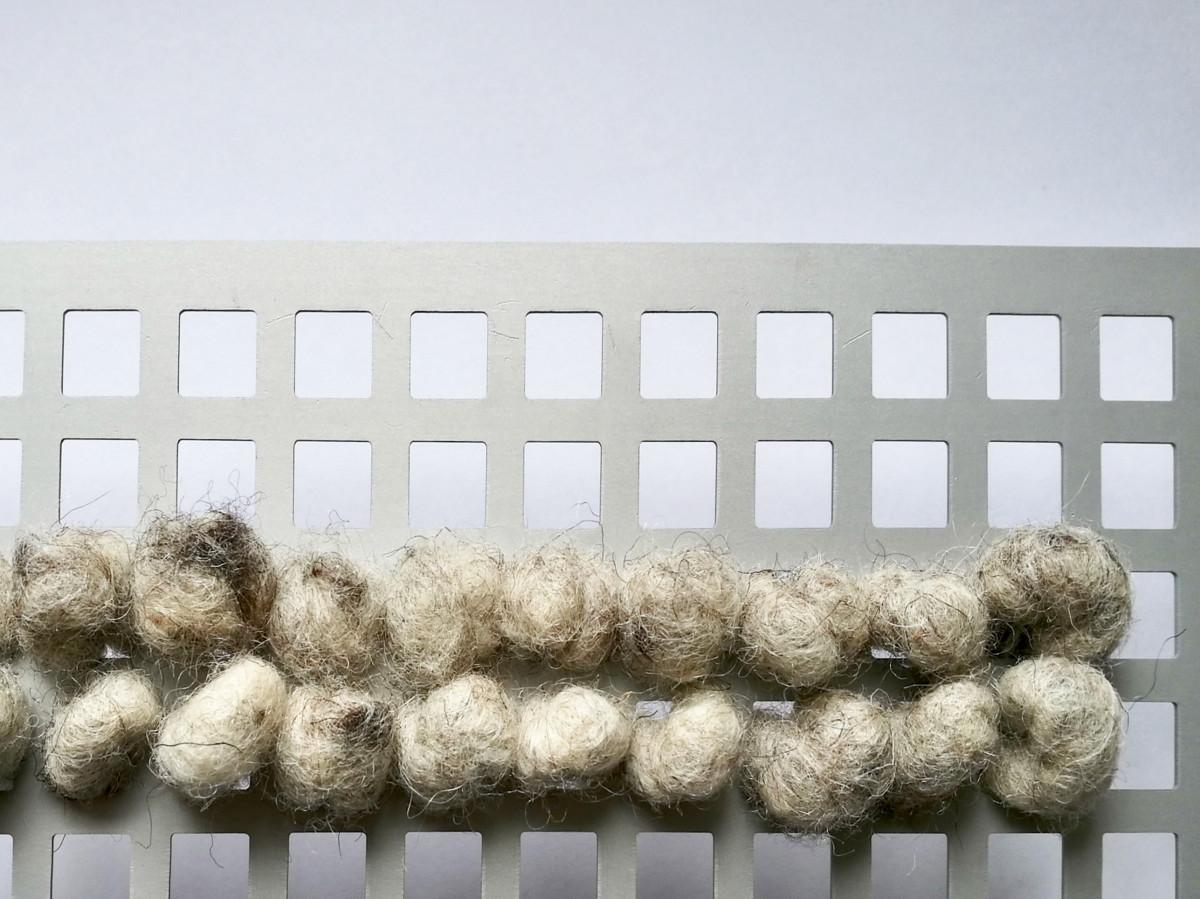 Quadratische Lochplatte mit Wolle